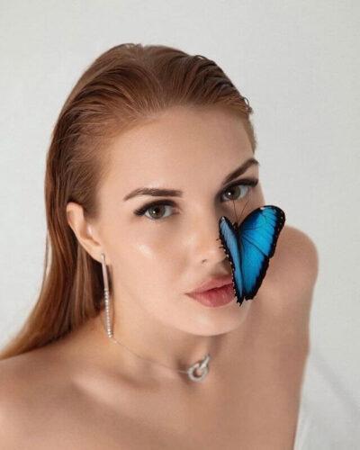 Живая бабочка сидит на носу у девушки