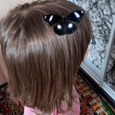 Hypolimnas bolina сидит на голове девочки